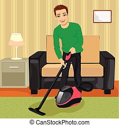 Young man cleaning carpet with vacuum cleaner at home - Full...