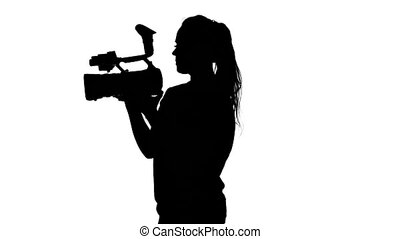 Operator holds the camera with two hands. White. Silhouette