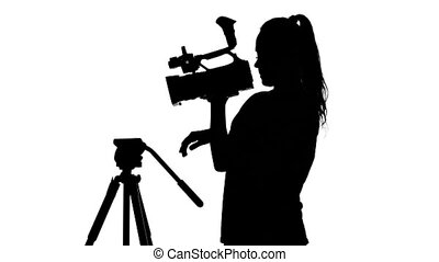 Girl is hooks the camera to the tripod. White. Silhouette -...