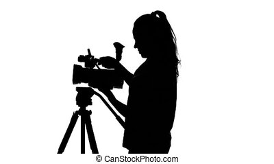 Girl fixes the camera on a tripod. White. Silhouette