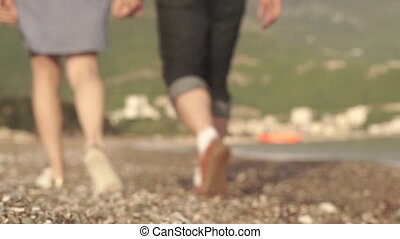 Loving couple walking along the coast holding hands and kissing blurred