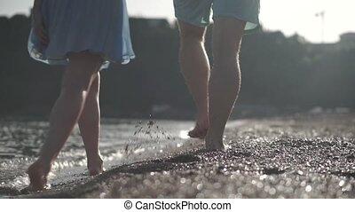A man in shorts and a girl in dress walking on the beach