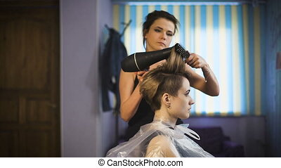 Business woman in a beauty salon, her makes hair styling.
