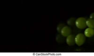 Sprig of green grapes on a platter on a black background -...