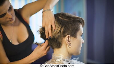 Beautiful girl in a beauty salon. Professional stylist makes...