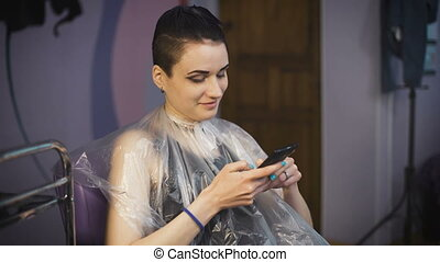 beauty, hairstyle and people concept - happy young woman with smartphone.