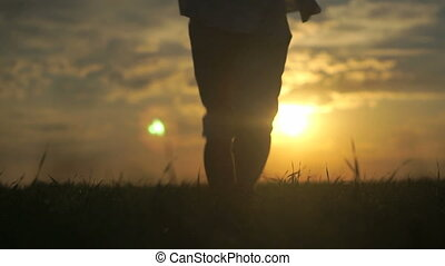Silhouette of man running towards beautiful sunset