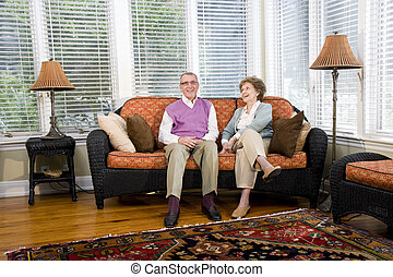 Happy senior couple sitting on living room couch - Happy...