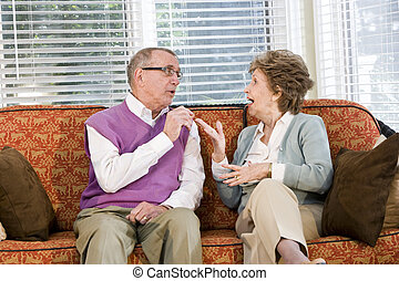 Senior couple chatting on living room couch - Senior couple...