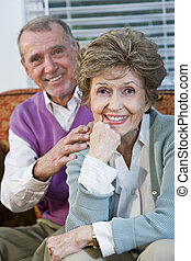 Loving senior couple sitting together on couch - Portrait of...