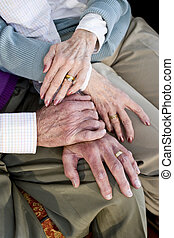 Close-up hands of senior couple resting on knees - Close-up...