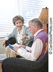 Senior couple chatting in living room reading book