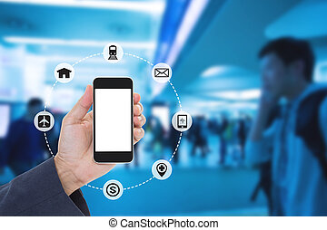 Hand holding mobile phone with blurred image of crowd