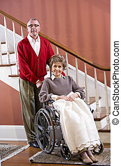 Senior couple at home, woman in wheelchair - Senior couple...