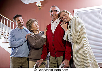 Elderly couple at home with adult children, senior man using...