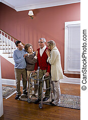 Elderly couple at home with adult children