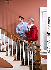 Man helping senior father climb stairs at home - Man helping...