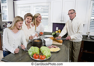 Three generation family in kitchen cooking lunch - Three...