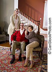 Senior couple at home on sofa with adult daughter