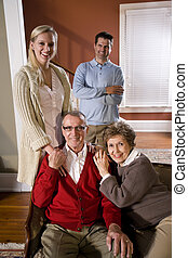 Senior couple at home on sofa with adult children - Portrait...