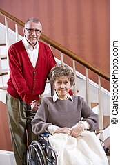 Senior couple at home, woman in wheelchair