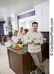 Man eating in kitchen with family in background - Mid-adult...