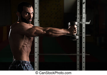 Shoulders With Dumbbells Exercise In A Gym - Young Man...