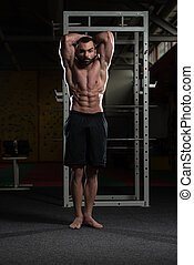 Young Bodybuilder Flexing Muscles - Portrait Of A Young...