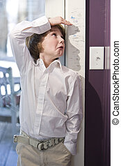 Young child measuring height on growth chart - Boy checking...