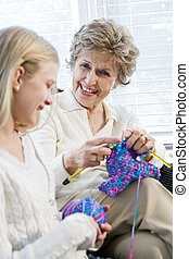 Grandmother knitting with granddaughter, focus on senior...