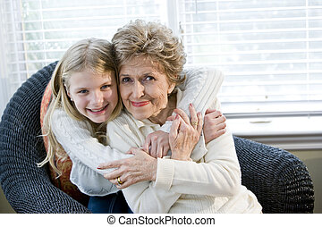 Portrait of happy young girl hugging grandmother