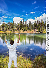 Middle-aged woman Sun Salutation on small lake - Jasper...
