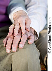 Hands of elderly couple touching on knee - Hands of...