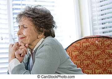 Elderly woman upset sitting alone by window with eyes shut