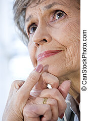 Close up face of senior woman thinking, hands on chin