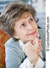 Face of serious elderly woman looking up - Face of elderly...