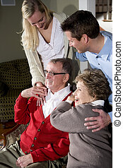 Senior couple with adult children together at home