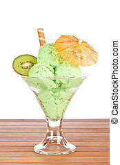 Delicious kiwi ice cream in glass with umbrella on wooden...
