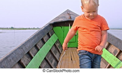Toddler boy enjoys the boat trip on the Inle Lake in Myanmar...
