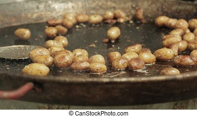 potato frying and being stirred on metal plate food festival