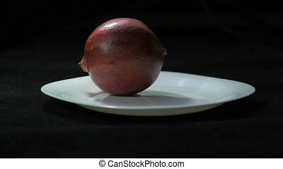 Whole pomegranate on white plate dolly shot clip