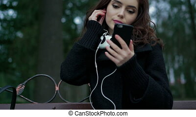 Beautiful girl listens to music in the park