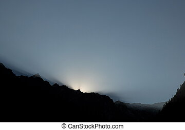 Shafts of sunlight behind clouds