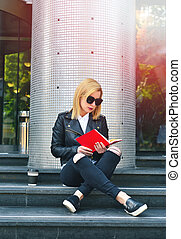 girl reading book - young hipster girl reading a red book...