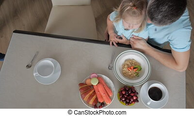 Happy kid girl and woman preparing healthy breakfast together - top view. Mother father and daughter.