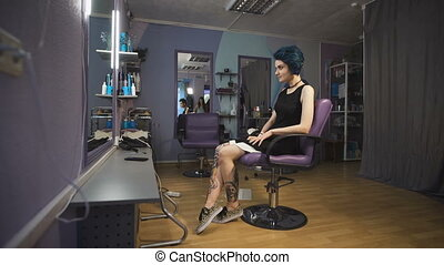 Punk girl with blue hair and tattooed legs in a beauty...