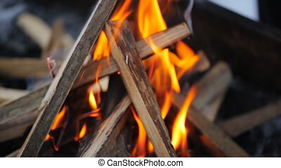 Bonfire with a strong flame in form of a hut in which puts...