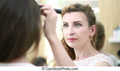 makeup artist applies makeup brush. beauty saloon