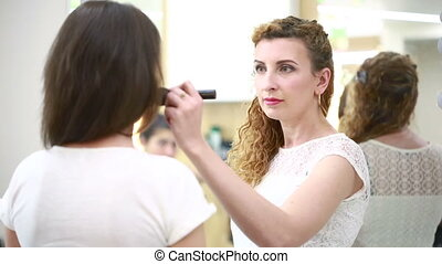 makeup artist applies makeup brush beauty saloon