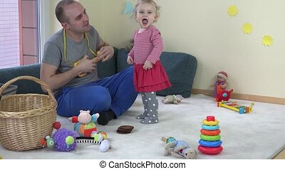 Father man play with toy guitar and happy toddler daughter...